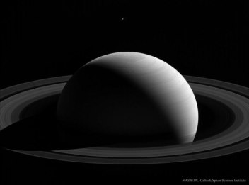 Tethys behind Saturn (Bonus: note hexagonal cloud pattern at the north pole)